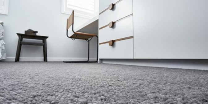 image closeup of textured grey wool carpet in bedroom setting